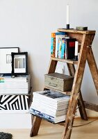 Old wooden stepladder used as shelves for books and magazines
