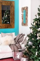 Decorated Christmas tree, pale couch and mirror on blue wall in living room