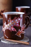 Colourful autumn leaves stuck on brown coffee mug