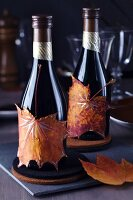 Small wine bottles decorated with painted autumn leaves