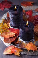 Tray of candles and painted autumn leaves