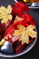 Small gift bags decorated with dried, painted autumn leaves