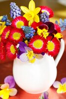 Spring bouquet with lawn daisies, hyacinth, narcissus and horned violets in a milk pitcher