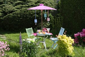 Garden table and chairs below Oriental parasol with party decorations