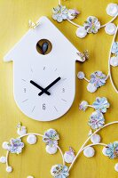 Garland of flower shapes punched out of maps next to wall clock