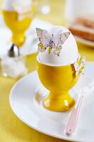 Butterfly shapes punched from old maps decorating boiled egg on breakfast table