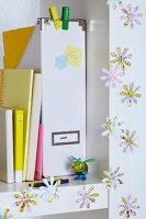 Flower shapes punched out of map decorating white shelving