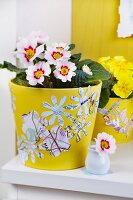 Flower and butterfly shapes punched out of maps decorating yellow flowerpots