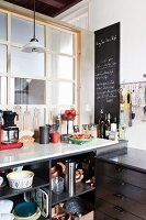 Marble kitchen worksurface with open shelves full of pots and pans, blackboard on wall and interior window partition in vintage, country-house kitchen