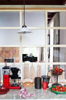 Marble kitchen worksurface, red coffee machine and nostalgic chopping boards leaning against vintage interior window