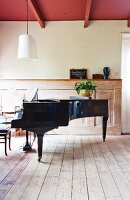 Black concert grand piano on board floor and vintage wood panelling on wall in renovated country house