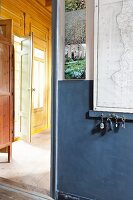 Key rack on dove blue wall with map and open doorway leading to room beyond