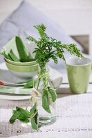 Pale green, felt pea pods draped around small glass vase decorating table