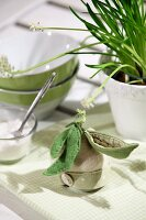 Egg cosy decorated with felt pea pods on pale green and white gingham place mat