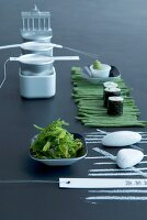 Table set with sushi, seaweed salad and beans