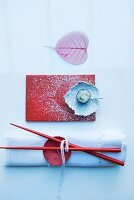 Decorative, Japanese place setting: white napkin with large button as napkin ring, chopsticks, red rectangular plate, leaf-shaped ceramic dish decorated with icing sugar