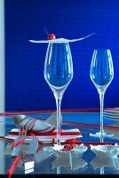 Oriental place setting: thin sheet of pastry and crab apple on stemmed glass