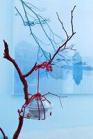 Oriental table decoration: crockery and cutlery wound around with red wool hanging from branch