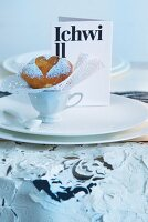 Unconventional menu card and muffin with icing sugar heart motif on wedding table