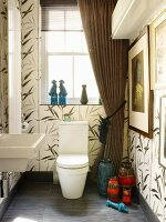 Large tiles with floral pattern in bathroom with draped curtains & collection of retro vases next to toilet