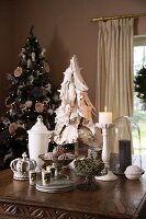 Christmas still-life arrangement on table - dish of fir cones, lit candles and white glass vessel in front of decorated Christmas tree in corner of room