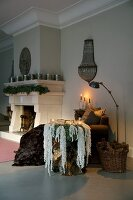 Opulent wreath of mountain lichen on side table and candlelight next to open fireplace with fir garland