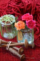 Pinks in preserving jar wrapped in green yarn and wooden spindles