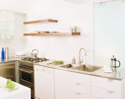Modern kitchen counter with white doors and stainless steel worksurface