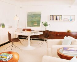 Retro-style living room with tulip sideboard and armchairs in foreground