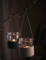 Tealight holders made from small, half-painted jam jars tied to branch with string