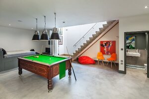 Pool room with antique pool table, trendy seating area, staircase leading upwards and view into modern wet room