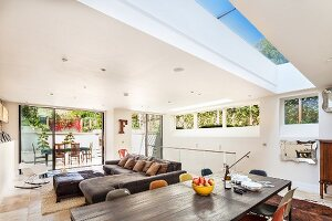 Modern extension with skylight and ribbon window - designer-style, open-plan living space with access to terrace