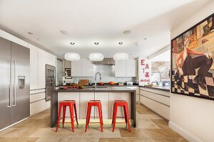 Designer kitchen with island counter, red bar stools, modern painting on wall and wall aperture leading to dining area