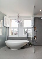 Free-standing designer bathtub in front of open wooden louver shutters and chandelier in grey bathroom with rainfall shower