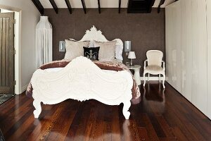 Majestic, postmodern double bed, white floor-to-ceiling wardrobe and dark, exotic wood parquet floor in bedroom