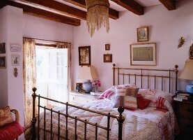 Hand-sewn quilts and scatter cushions on brass bed in romantic bedroom of historical farmhouse