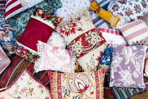 Collection of handmade cushions in elegant, classic fabrics decorated with trims and fringes