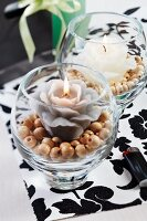 Candle lanterns with flower-shaped candles on wooden beads on black and white place mat