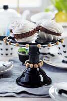 Filled meringues on black glass cake stand decorated with strings of wooden beads