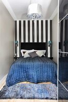Quilted bedspread on double bed with black headboard against black and white striped wallpaper in narrow niche and rug on wooden floor at foot of bed