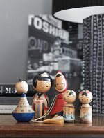 Family of wooden, painted Kokeshi dolls on wooden surface next to partially visible table lamp
