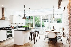 Modern, open-plan interior with exposed brickwork - dining area and kitchen in front of terrace doors