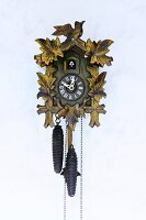 Traditional cuckoo clock with pendulum mounted on wall