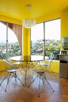 Classic, transparent, plastic shell chairs and round table in corner of yellow-painted room with panoramic windows