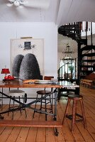 Former workbench used as dining table in front of picture on wall in open-plan interior; black, metal spiral staircase in background