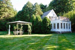 Laube und weiss getünchtes Wohnhaus mit Anbau und Dachterrasse in grosser Garten