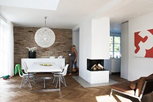Open-plan interior with dining area, free-standing fireplace block and herringbone parquet floor; exposed brick wall behind dining area