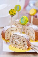 Slices of lemon Swiss roll decorated with toothpicks and bottle tops on white china plate