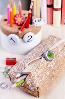 Full pencil case with zip decorated with bottle top; pen holder decorated with bottle tops printed with numbers