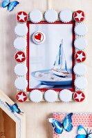 Wooden picture frame decorated with bottle tops painted red and white